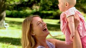 Moeder die haar babymeisje in de lucht opheffen stock video
