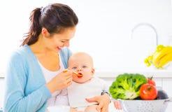 Moeder die haar Babymeisje met een lepel voeden Stock Foto