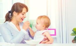 Moeder die haar Babymeisje met een lepel voeden Ruwe macaroni op witte achtergrond royalty-vrije stock afbeelding