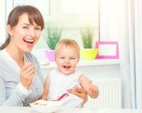 Moeder die haar Babymeisje met een lepel voeden Ruwe macaroni op witte achtergrond stock afbeeldingen