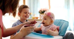 Moeder die haar Babymeisje met een lepel voeden stock afbeelding