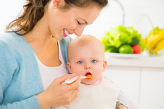 Moeder die haar babymeisje voeden Royalty-vrije Stock Afbeeldingen