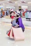 Moeder die haar dochter in de kledingsopslag kussen Stock Foto