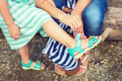Moeder die haar dochter helpen om op de zomersandals te zetten Stock Afbeeldingen