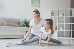 moeder die haar dochter helpen om streng te doen stock afbeelding
