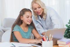 Moeder die haar dochter helpen om thuiswerk te doen Royalty-vrije Stock Fotografie