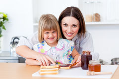 Moeder die haar dochter helpt het ontbijt voorbereiden Royalty-vrije Stock Foto's