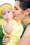 Moeder die haar dochter kussen Stock Foto