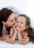Moeder die haar dochter kust Stock Afbeeldingen
