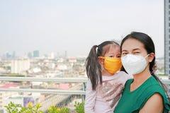 Moeder die haar dochter met het dragen van een beschermingsmasker tegen PM 2 vervoeren luchtvervuiling 5 in de stad van Bangkok t stock foto