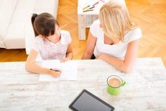 Moeder die haar dochter met het thuiswerk helpt Royalty-vrije Stock Foto