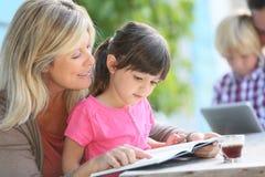 Moeder die haar dochter onderwijzen hoe te lezen stock afbeelding