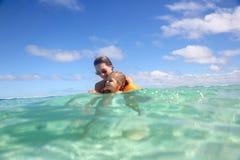 Moeder die haar dochter onderwijzen om in het overzees te zwemmen royalty-vrije stock afbeelding