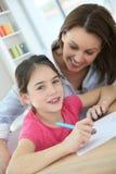 Moeder die haar dochter onderwijzen om te schrijven royalty-vrije stock afbeeldingen