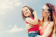 Moeder die haar dochter op wapen houden Stock Foto's