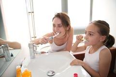 Moeder die haar dochter tonen hoe te om tanden te borstelen royalty-vrije stock foto