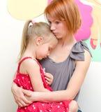 Moeder die droevig kind koesteren Stock Foto