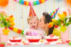 Moeder die haar gelukkige baby kust Royalty-vrije Stock Afbeeldingen