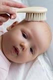 Moeder die of haar kammen borstelen weinig leuk babymeisje na bathi stock foto