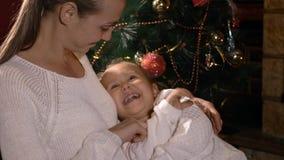 Moeder die haar kietelen weinig leuke dochter terwijl zij zitting op moeder` s handen stock video