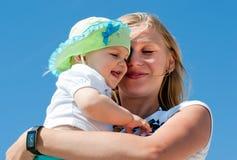 Moeder die haar kind omhelst Stock Fotografie