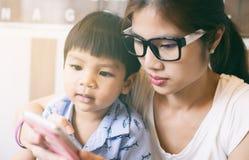 Moeder die haar kind onderwijzen om slimme telefoon te gebruiken stock fotografie