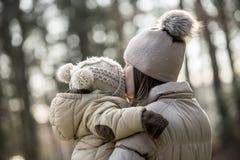 Moeder die haar kind in openlucht kussen Stock Afbeelding