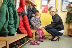 Moeder die haar kind van een Kleuterschool in garderobe 2 opnemen Stock Fotografie
