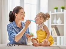 Moeder die haar kind voeden Stock Afbeeldingen
