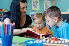 Moeder die haar kinderen homeschooling Stock Afbeelding