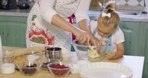 Moeder die haar kleine dochter onderwijzen om te bakken stock footage
