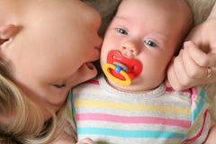 Moeder die haar kust weinig baby Stock Afbeeldingen