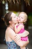 Moeder die haar kust weinig dochter Stock Foto's