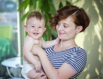 Moeder die haar 6 maand oude baby houden stock afbeelding
