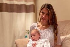 Moeder die haar meisje van de babyzuigeling in haar wapens houden royalty-vrije stock foto's