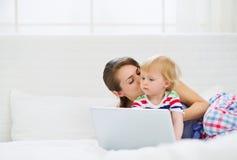Moeder die haar moderne baby kust die aan laptop werkt Stock Afbeeldingen