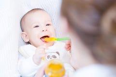 Moeder die haar mooie babyjongen met lepel voeden Stock Foto