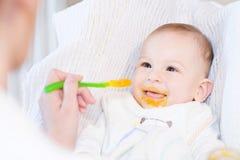 Moeder die haar mooie babyjongen met lepel voeden Royalty-vrije Stock Foto's