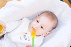 Moeder die haar mooie babyjongen met lepel voeden Royalty-vrije Stock Afbeeldingen