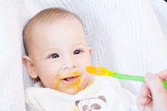 Moeder die haar mooie babyjongen met lepel voeden Royalty-vrije Stock Fotografie