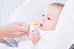 Moeder die haar mooie glimlachende babyjongen met lepel voeden Royalty-vrije Stock Afbeelding