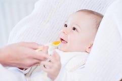 Moeder die haar mooie glimlachende babyjongen met lepel voeden Stock Foto