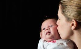 Moeder die haar nieuw kussen - geboren baby stock foto's