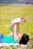 Moeder die haar omhoog opheft weinig dochter Stock Afbeeldingen