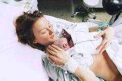 Moeder die haar pasgeboren baby na arbeid in het ziekenhuis houdt stock fotografie