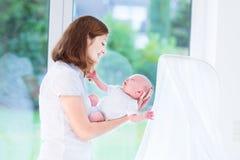 Moeder die haar pasgeboren baby naast voederbak houden Stock Foto's