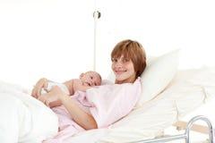 Moeder die haar pasgeboren baby omhelst Stock Fotografie