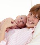 Moeder die haar pasgeboren baby omhelst Stock Afbeeldingen