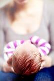 Moeder die haar pasgeboren baby wiegen Stock Afbeeldingen