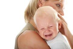 Moeder die haar schreeuwende baby geïsoleerd_ houdt Stock Afbeeldingen
